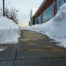 sidewalk beside building with snow removal after blizzard